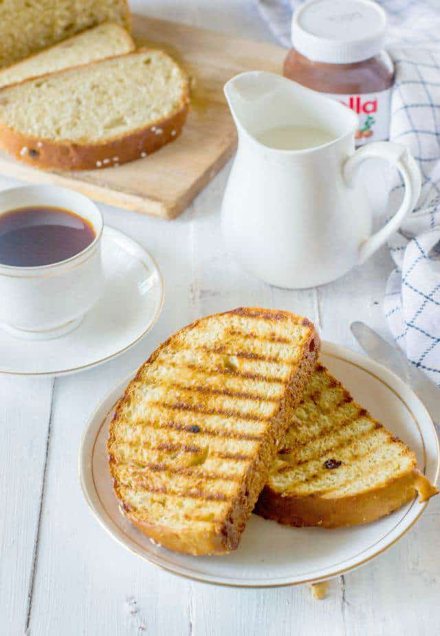 Toasted slices of artos greek celebration bread on a white plate along with a cup of tea