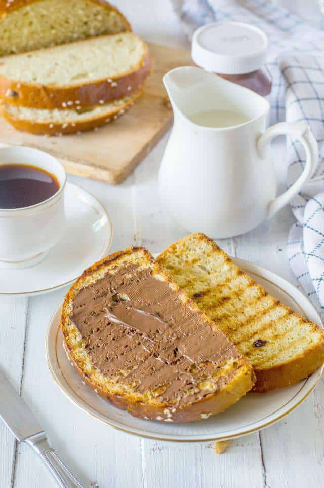Nutella spread on a slice of artos greek celebration bread serve along with a cup of tea and a jug of milk