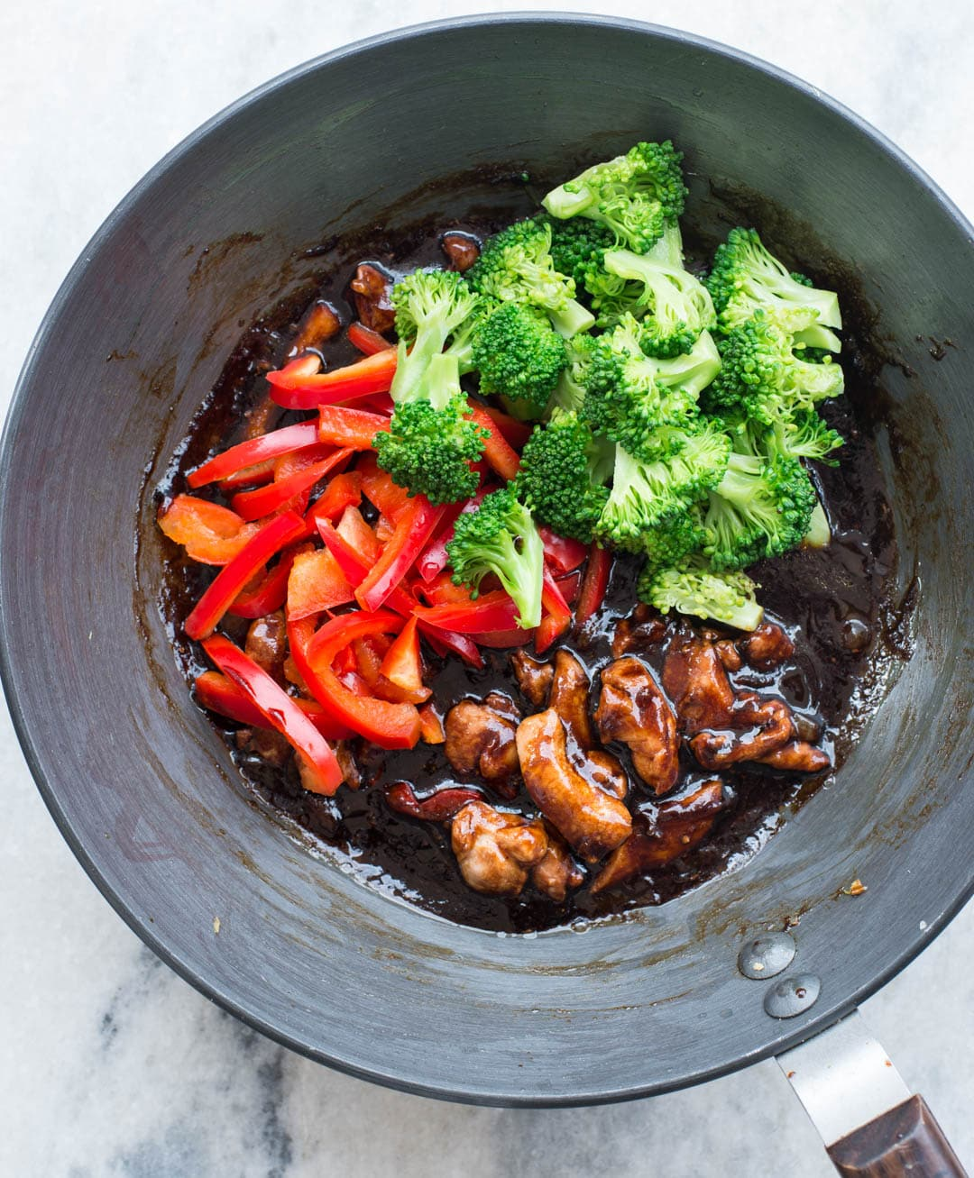 Vegetables like chili-peppers and broccoli added to chicken cooked in asian stir fry sauce in a wok.