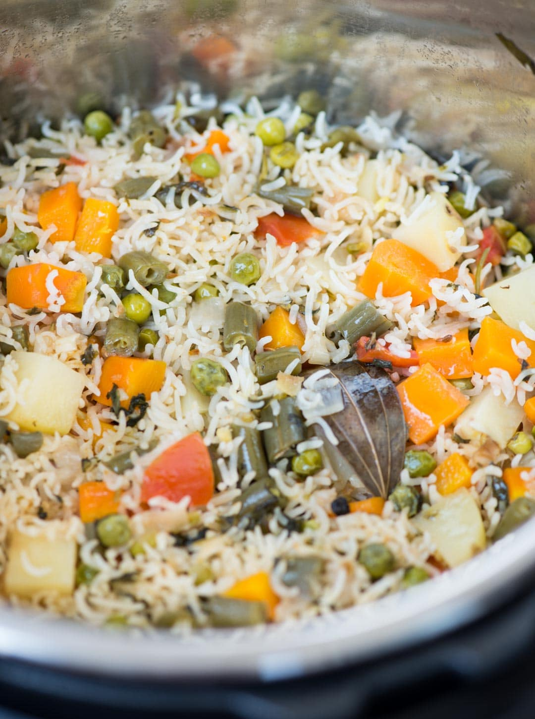 Veg Pualo is an Indian style rice pilaf made with long grain basmati rice, an array of vegetables and whole spices. This fragrant one-pot dish can be made on stove top, in a pressure cooker or in an Instant Pot.