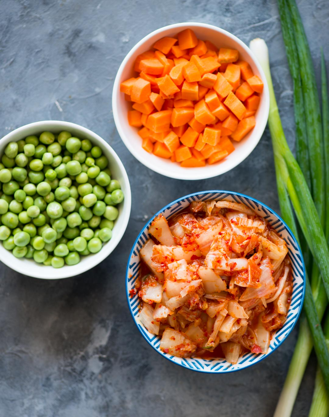 Quick and easy Kimchi Fried rice with tons of flavour from Kimchi, Garlic, ginger and gochujang. Throw in some peas, carrots and top it with sunny side up for a delicious meal.