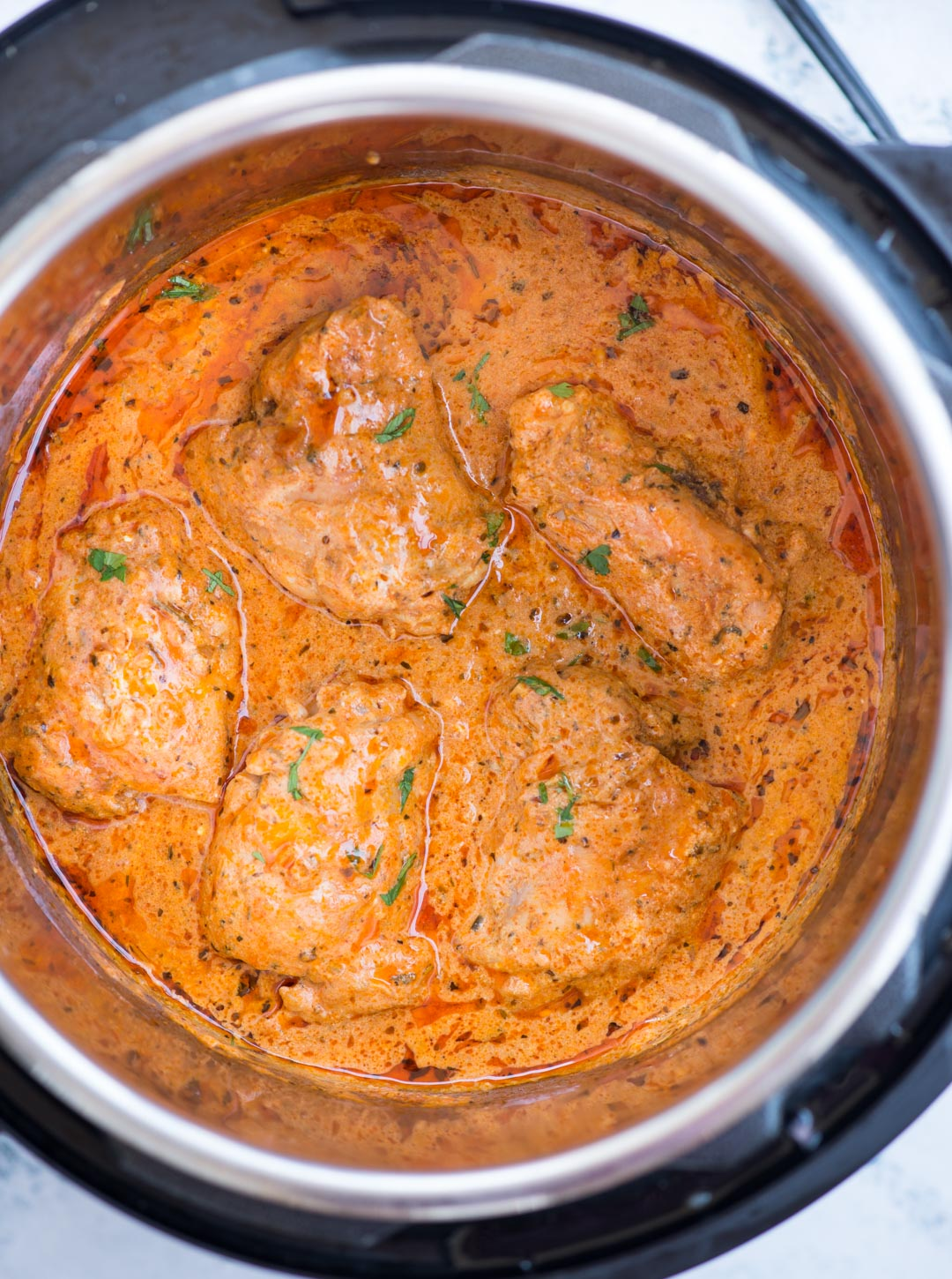 Instant Pot Chicken in a creamy tomato sauce with juicy chicken thighs, buttery tomato sauce is incredibly delicious and takes less than 30 minutes to make.