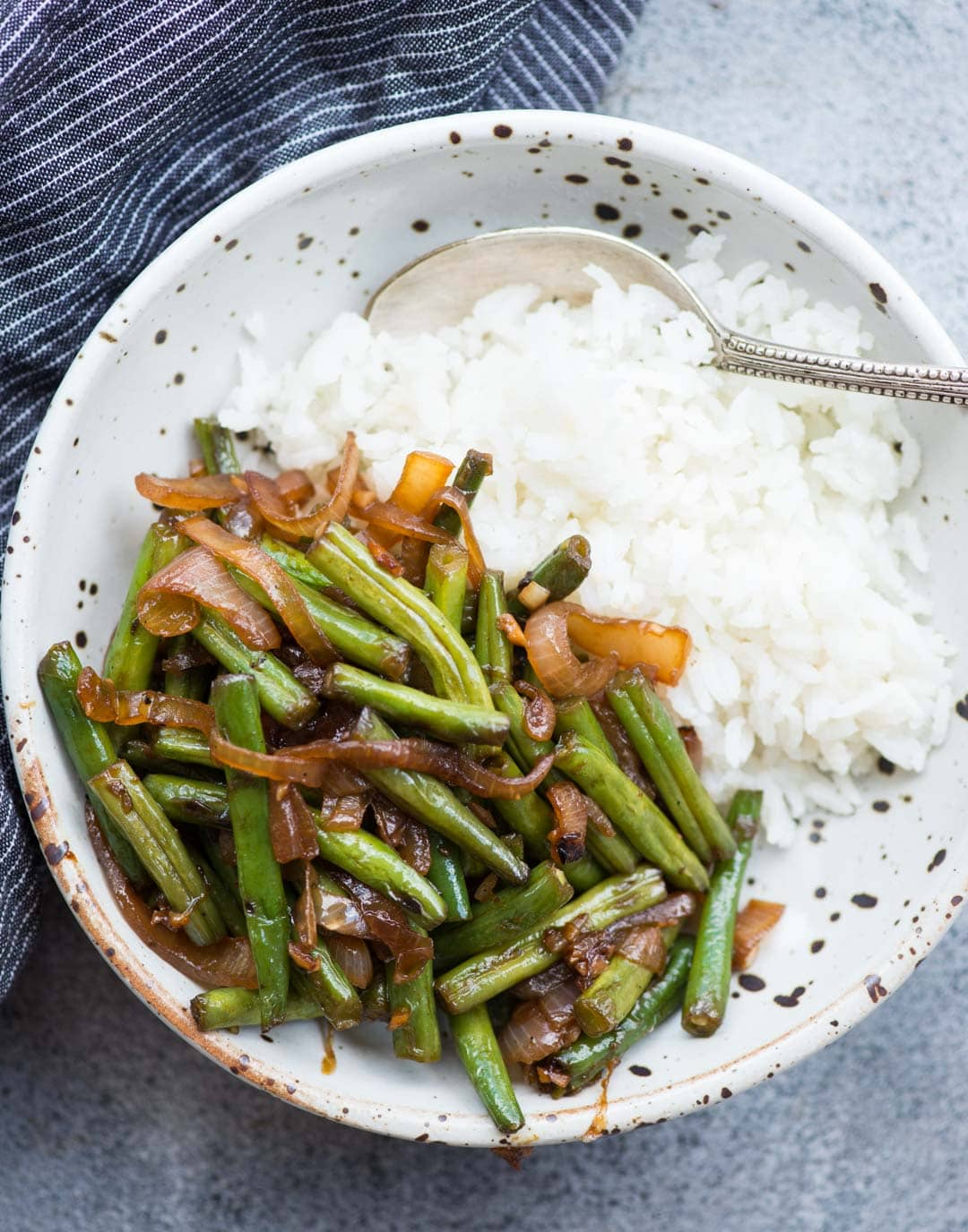 Asian Sauteed Green Beans with caramelized onion, garlic and a dash of soy sauce is an easy and versatile side dish. It takes only 20 minutes to make,the beans turn out tender and crispy.