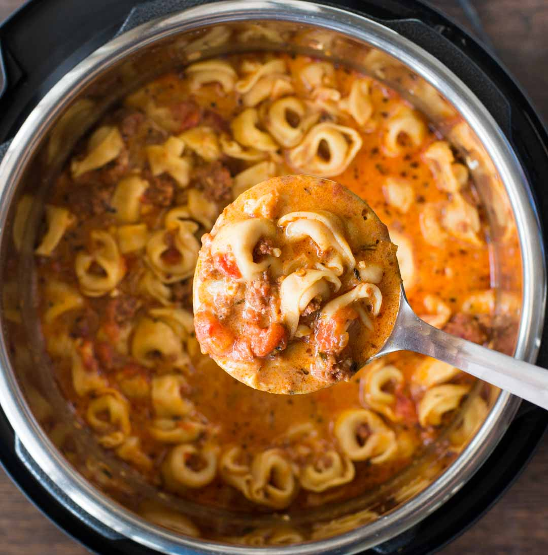 This cosy  Sausage Tortellini Soup is delicious and takes less than 15 minutes to make in an Instant Pot. A bowl of Creamy Tomato based broth, Sausage, Cheesy soft Tortellini and a generous sprinkle of Parmesan is filling and flavorful.