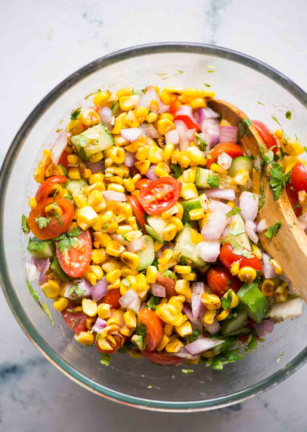 Fresh Roasted Corn Salad is packed with sweet corns, cucumber, tomato, onion and tossed in a lemony vinaigrette. Charred corn ads a lot of flavour to the salad. This quick salad is a perfect side dish in summer BBQs or for potlucks.