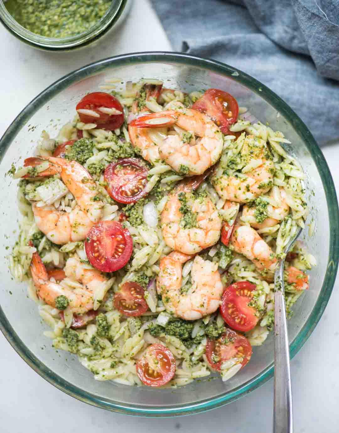 Orzo salad is loaded with Juicy shrimp, cherry tomatoes, onion and everything is tossed in fresh basil pesto. This refreshing salad can be served as a main dish or as a side dish in summer barbeque.