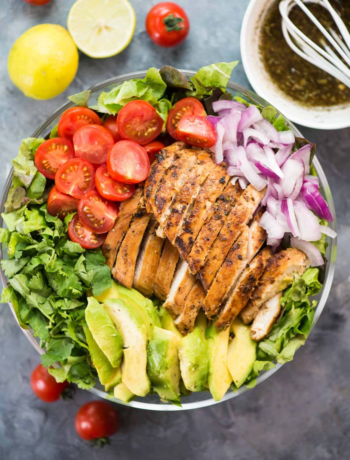 Avocado-Hühnersalat mit einer erfrischenden Kräutervinaigrette ist mit frischem Gemüse, gebratenem Hühnchen und cremiger Avocado beladen.  Es ist knusprig, cremig und ein wirklich füllender Salat.