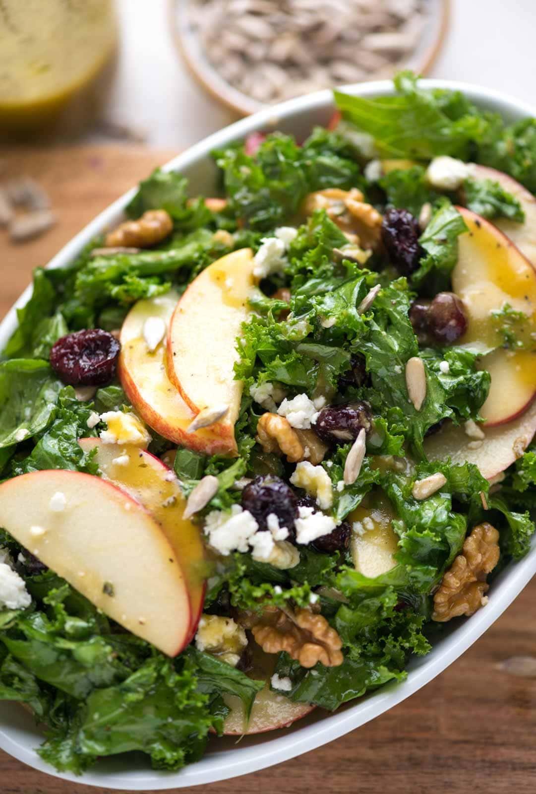 Bowl of Apple Kale Salad - Apple cider vinaigrette drizzled over Sliced apples, feta, walnut, cranberries and sunflower seeds.