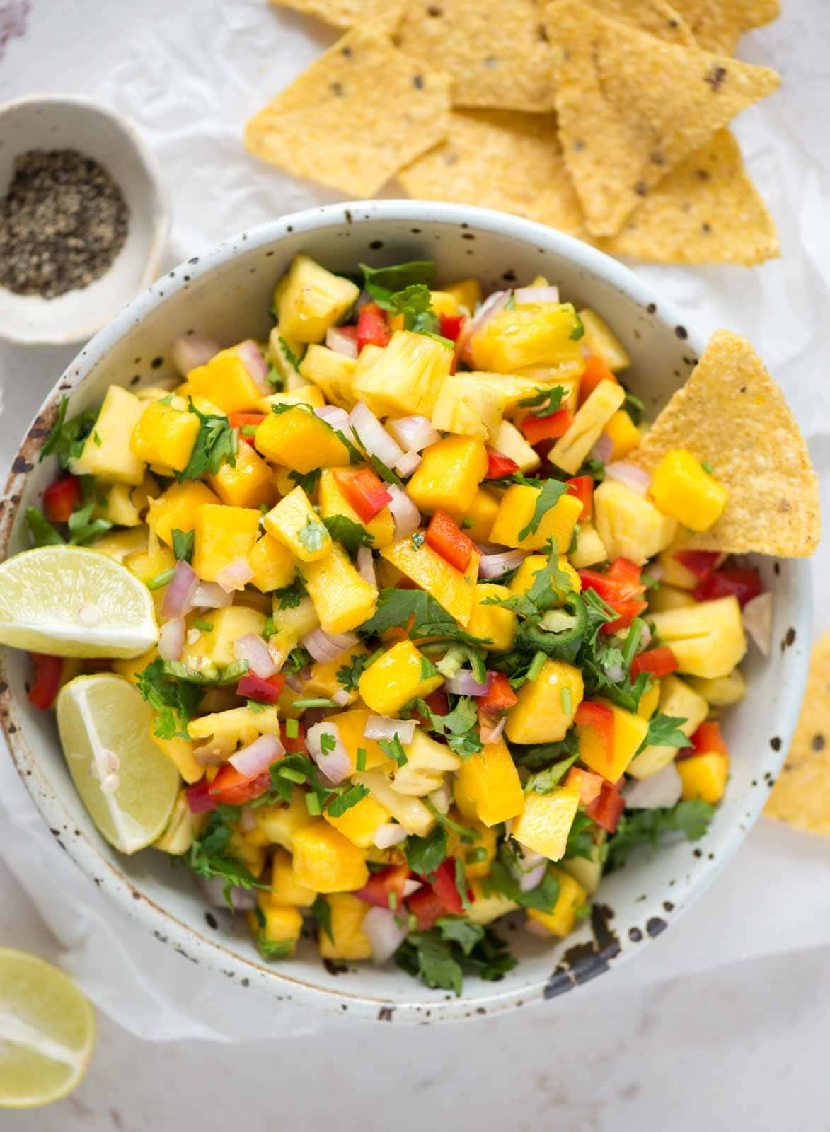 A sweet and spicy super easy salsa recipe that has two yum fruits - pineapple and mango. Pineapple Apple Salasa makes for the perfect summer treat with chips.