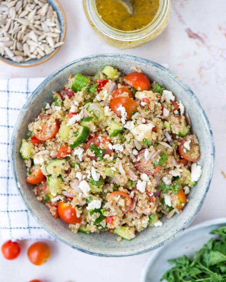 Featured image of Quinoa salad in a bowl along with vinaigrette decoratively put on a table with seeds, herbs and cherry tomato