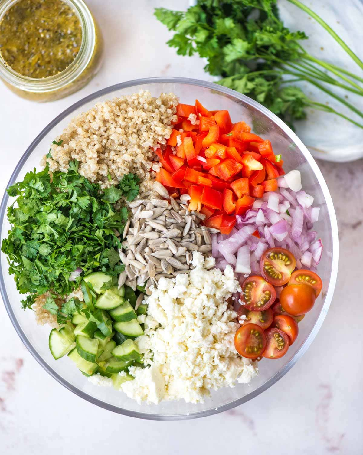 Ingredients required to make quinoa salad - quinoa, cherry tomato, herbs, cucumber, sunflower seeds, onion.