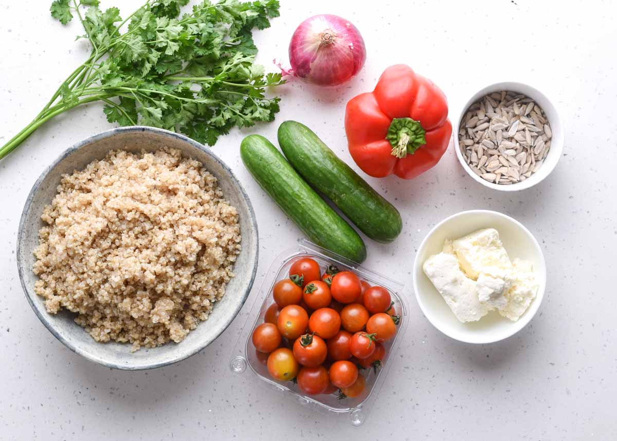 Quinoa Salad Ingredients laid out on the surface - quinoa, cherry tomato, peta cheese and vegetables.