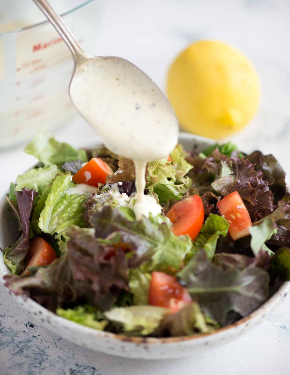 Picture of spoonful of Italian Parmesan Peppercorn dressing added to a leafy vegetable salad in a bowl.
