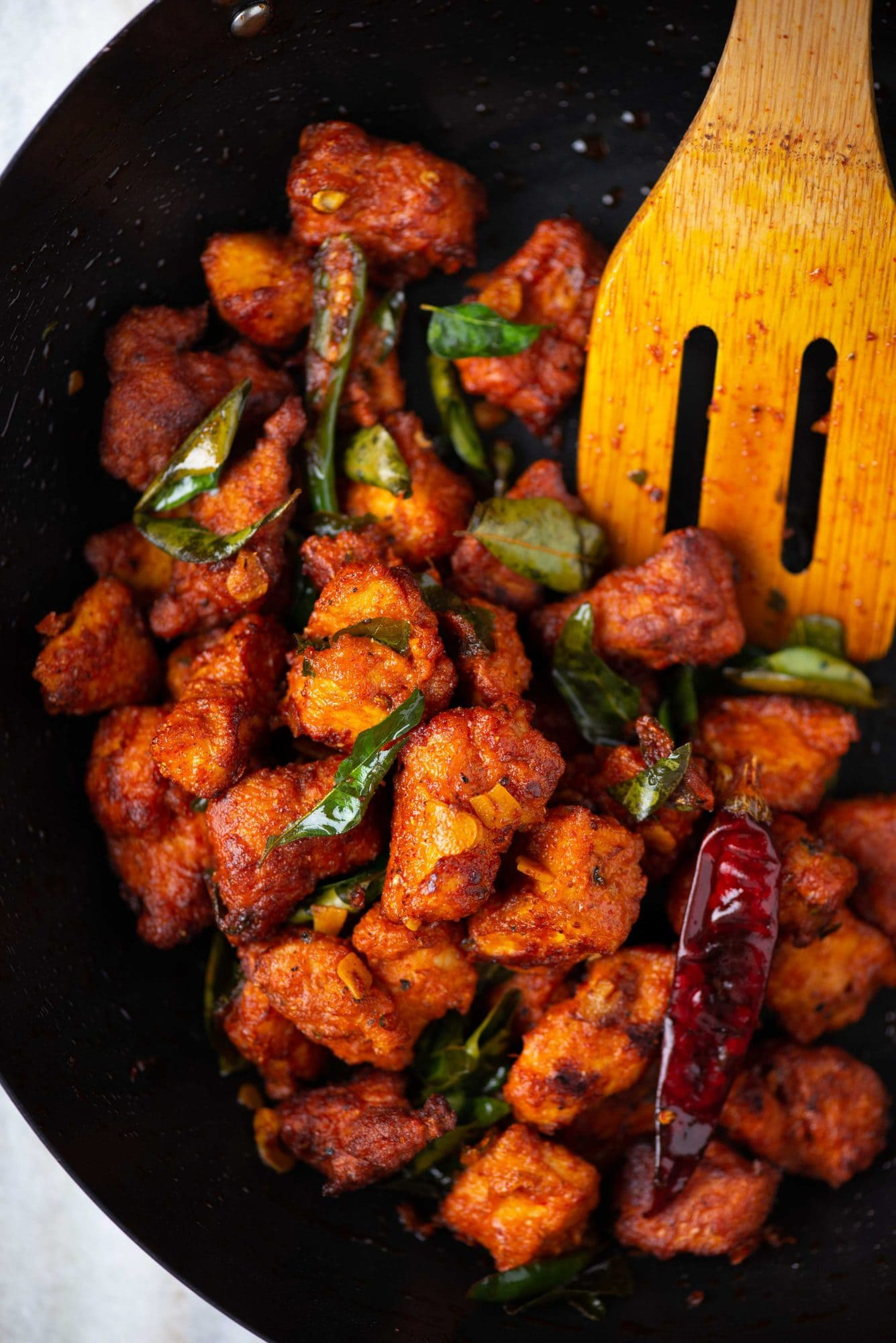 Close-up picture of spicy chicken 65 made with red chillies and curry leaves.