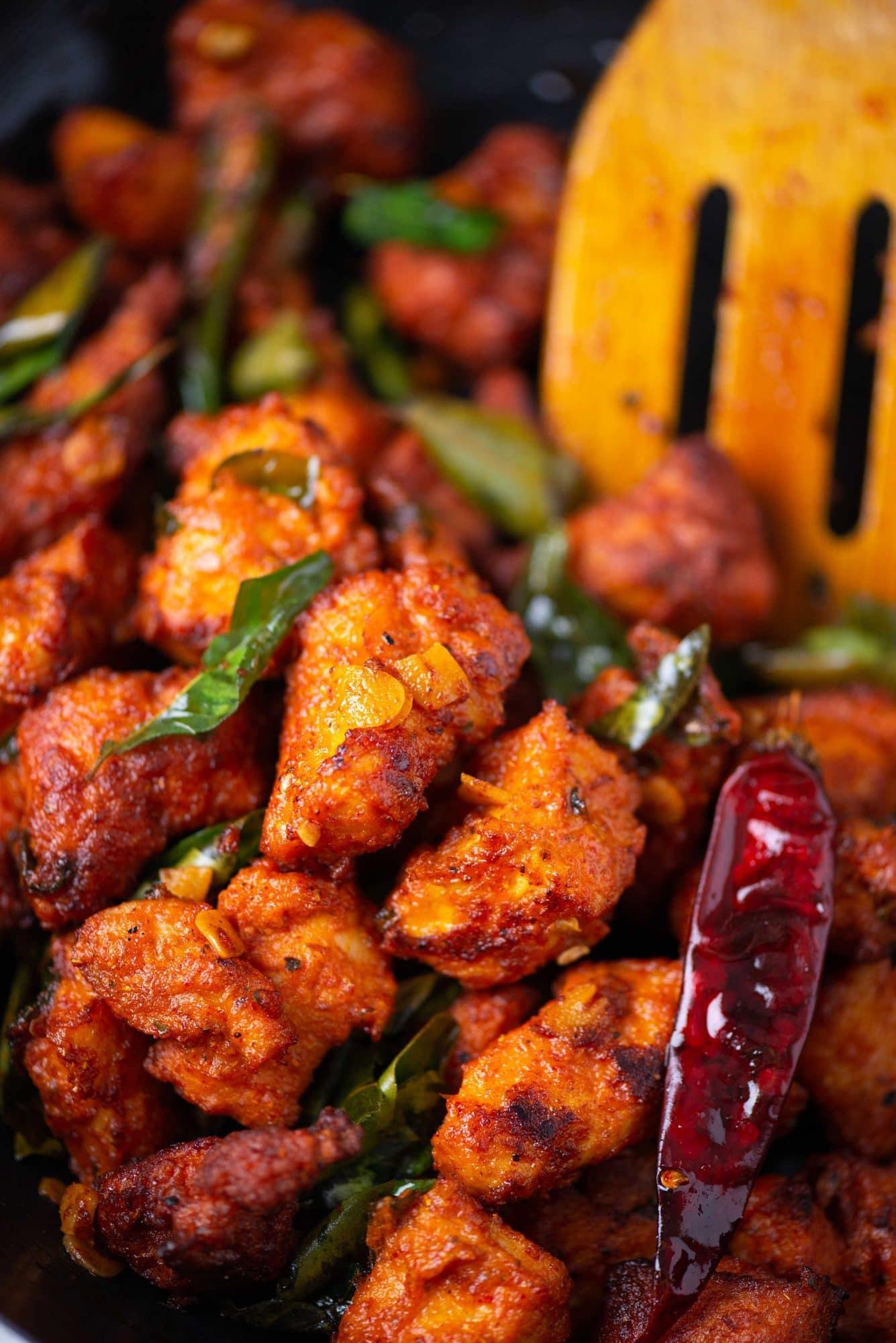 Close up shot of spicy chicken 65 appetizer shown with red chillies and curry leaves.