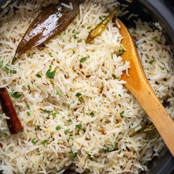 Picture of Jeera rice cooked in a Dutch oven with spices like bay leaf, cumin, cinnamon and chopped coriander leaves sprinkled on top.