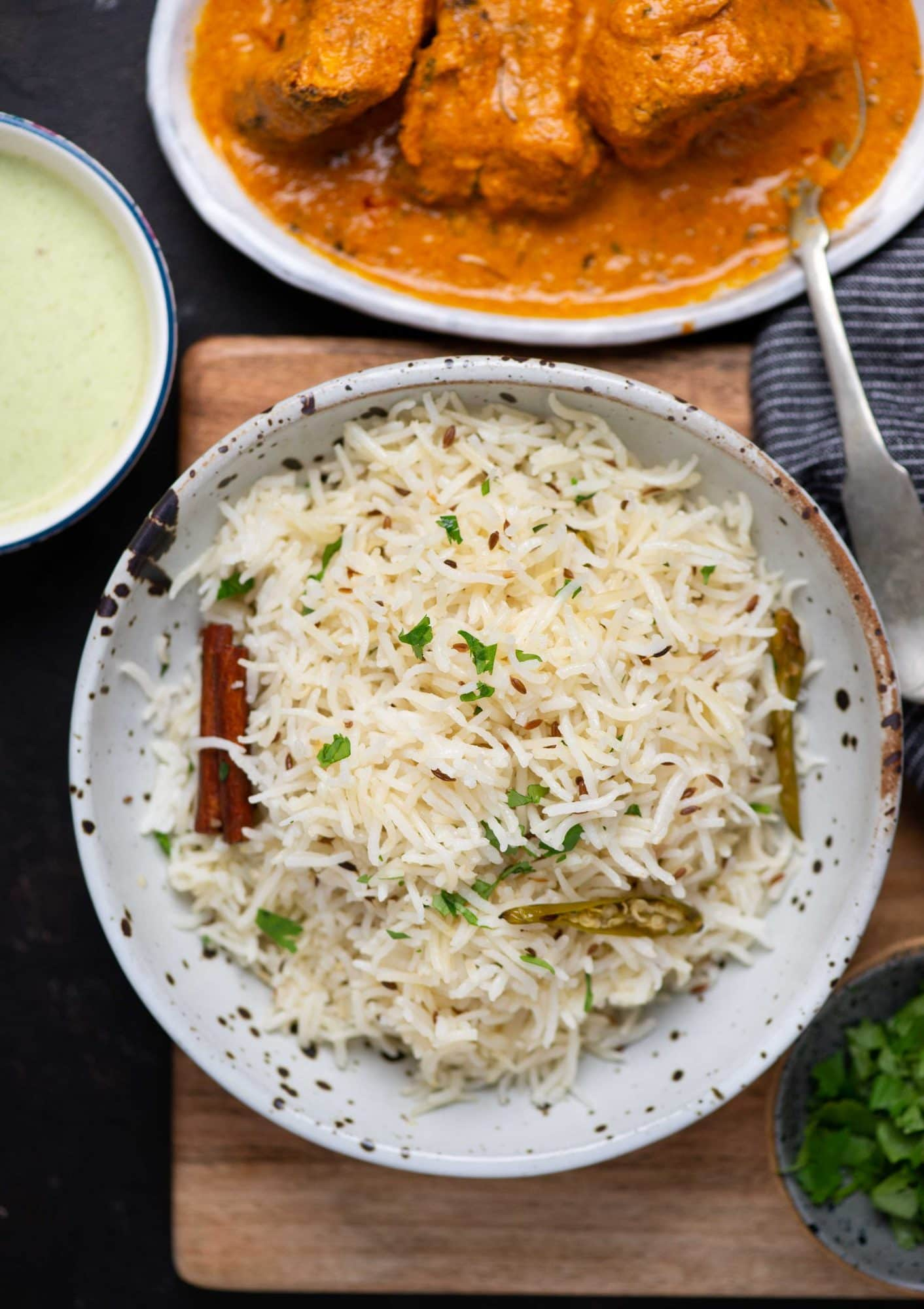 picture of Jeera rice served on a plate with gravy and a mint chutney served along with it