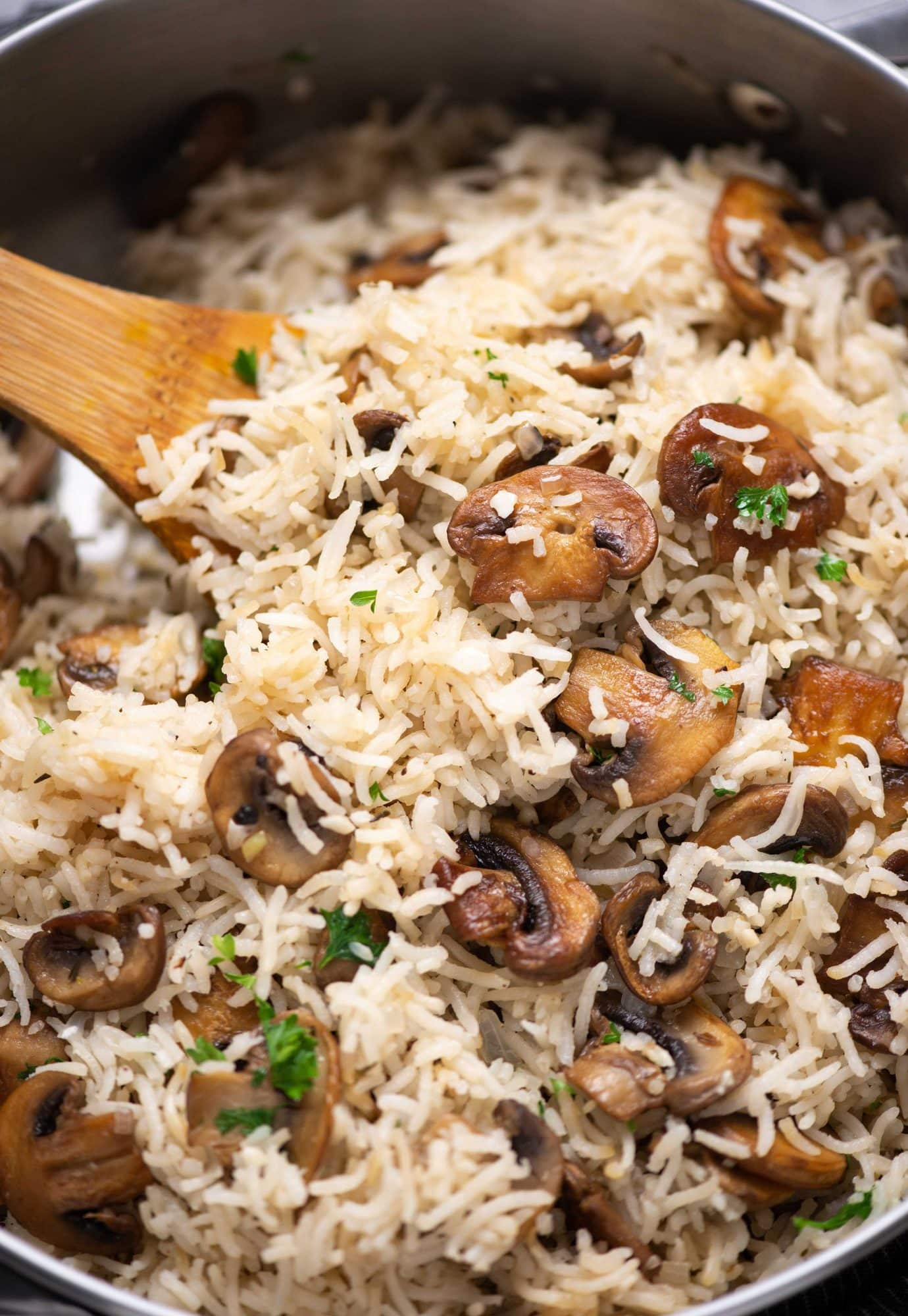 Close-up shot of Mushroom rice with brown sauteed bits of mushroom and garnished with parsley