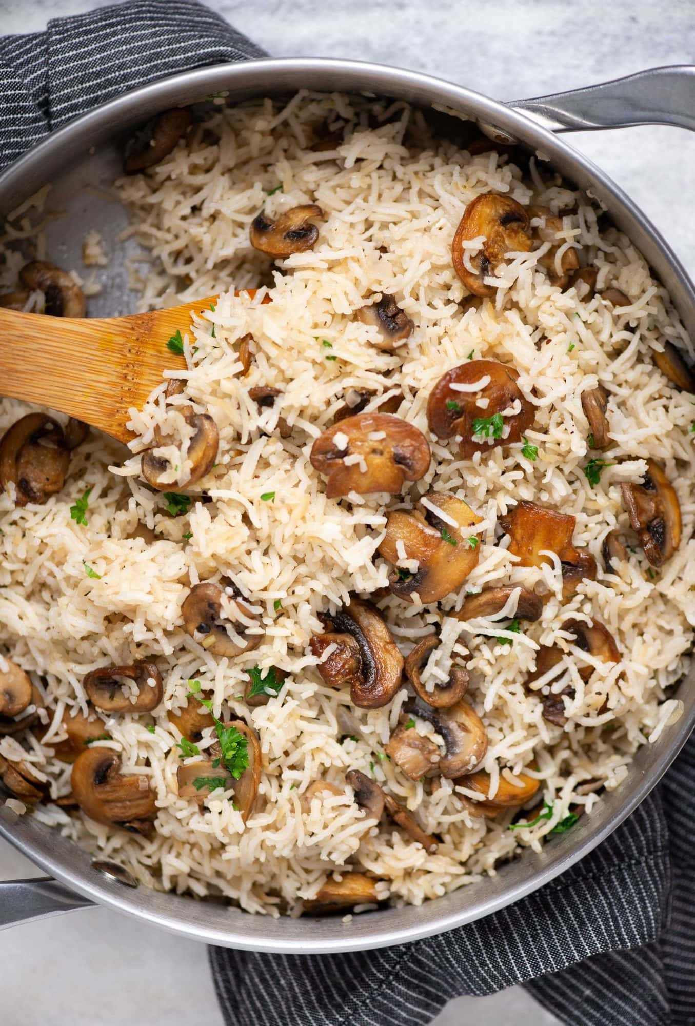Mushroom rice made as a one-pot dish shown in a pot with brown colored rice and sauteed mushrooms.