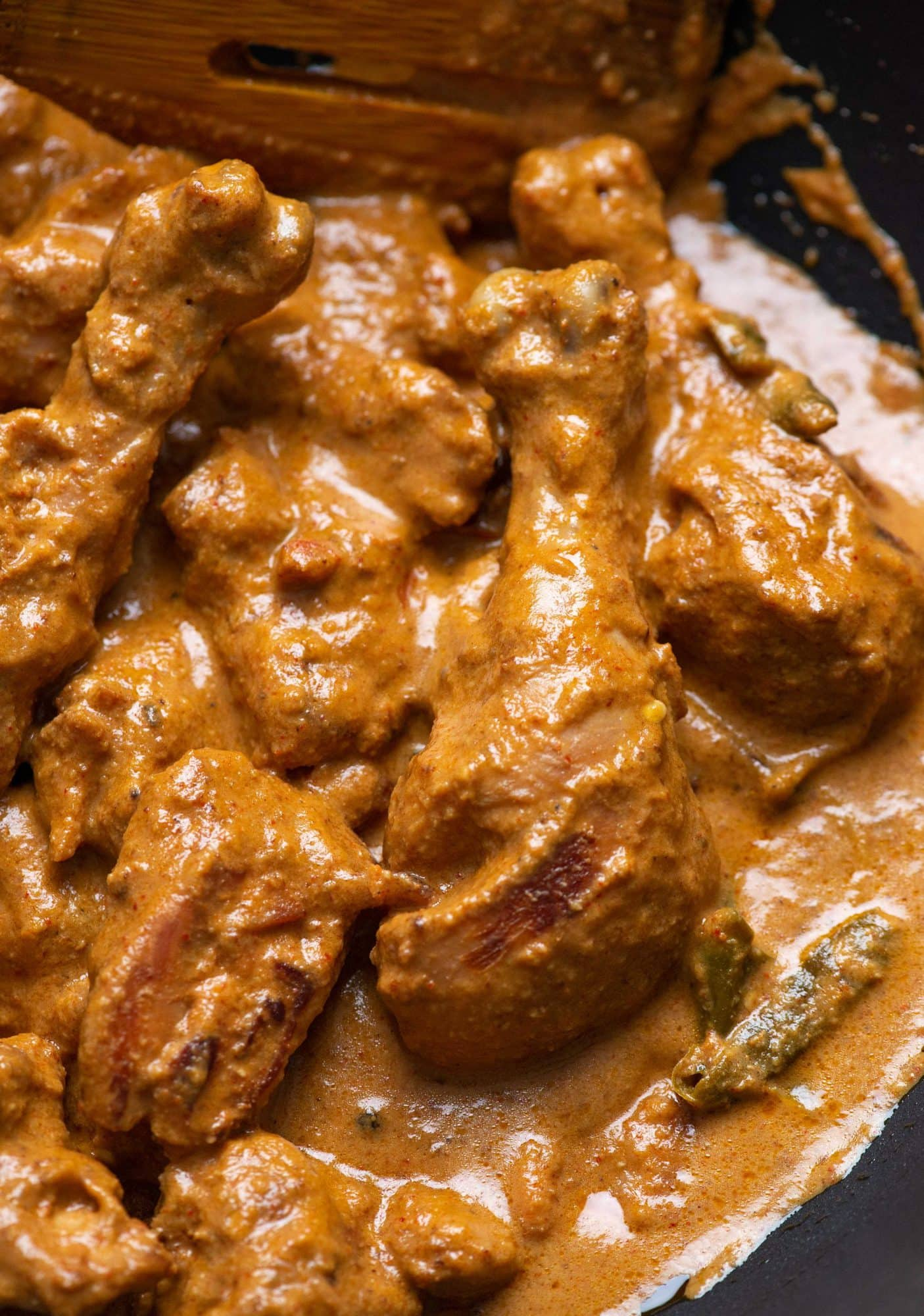 Close up picture of rich and creamy chicken korma being cooked in a kadhai/skillet.
