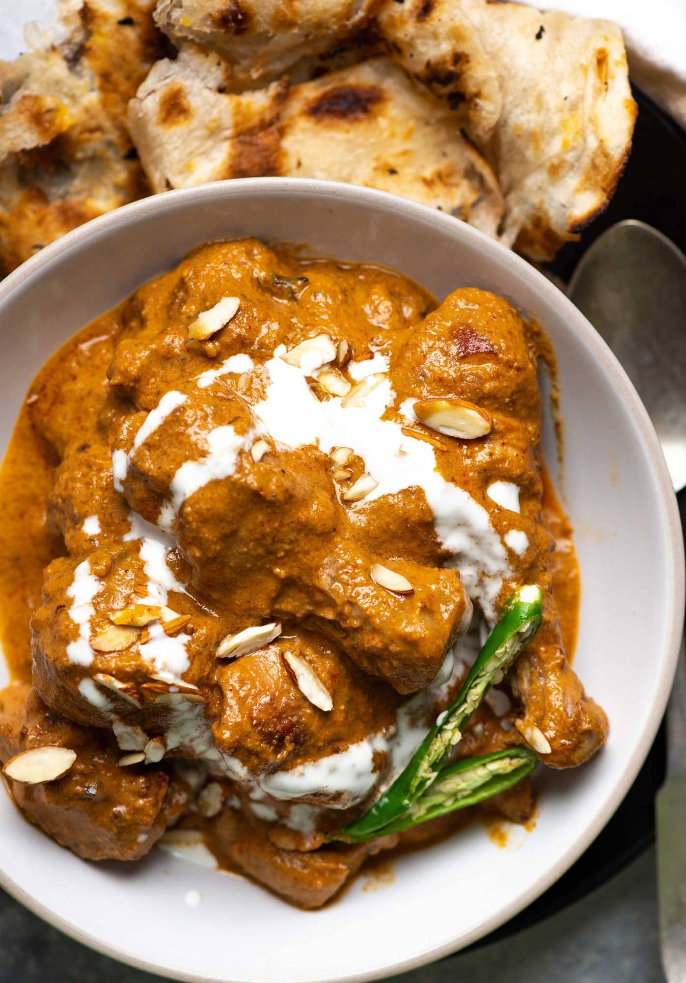 Chicken korma in a white plate with chillies, almonds and cream.