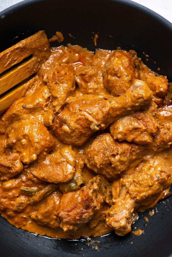 Rich and creamy Indian chicken korma curry being cooked in a skillet/kadhai.